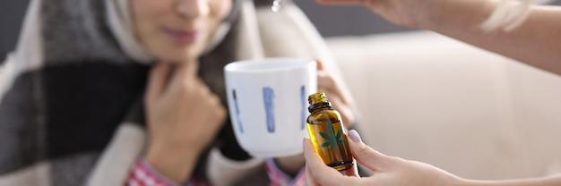 Mulher pingando óleo de maconha no copo. combatendo o estresse com o conceito de maconha