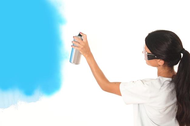 Mulher pinta a parede em azul sobre fundo branco