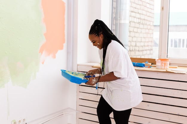Mulher pinta a parede