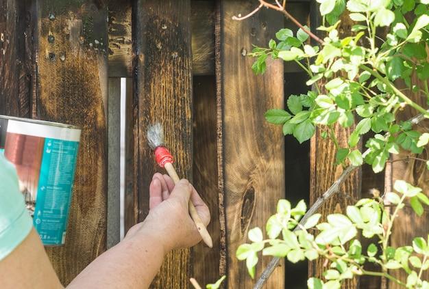 Mulher pinta o terraço de madeira com um pincel
