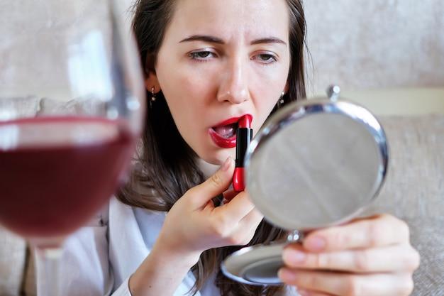 Mulher pinta os lábios de batom bêbados com um copo de vinho