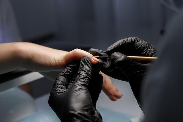 Mulher pinta unhas com gel em salão