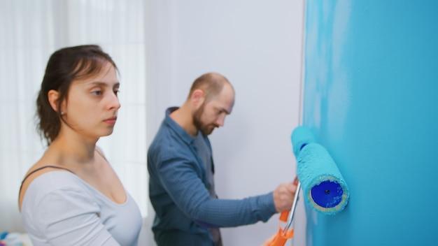 Mulher pintando a parede com escova de rolo enquanto redecora a sala de estar do apartamento. casal redecorando juntos. redecoração de apartamento e construção de casa durante a reforma e melhoria. reparar e remover
