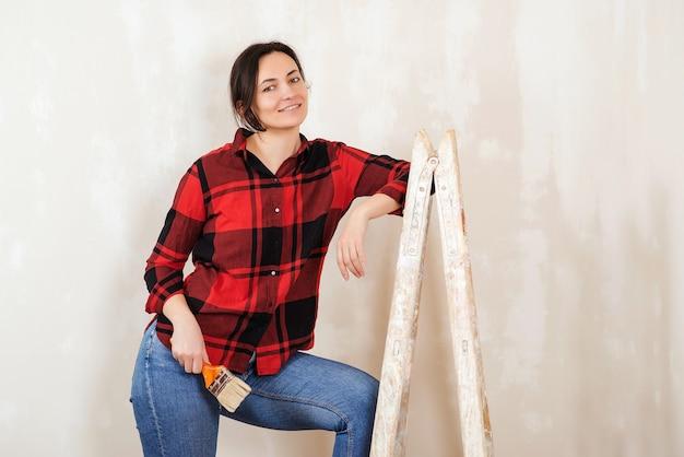 Mulher pintando a parede interior com rolo de pintura na casa nova. conceito de decoração para casa. reparação de apartamento.