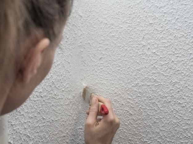 Mulher pintando a parede. restauração das paredes brancas pintadas.