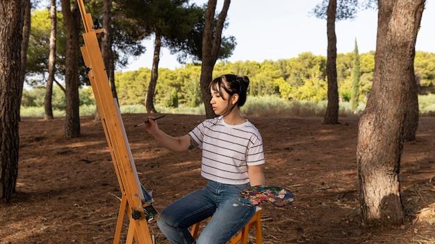 Mulher pintando ao ar livre com tela e paleta