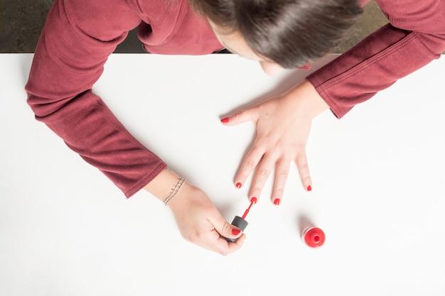 Mulher pintando as unhas em vermelho. acima vista