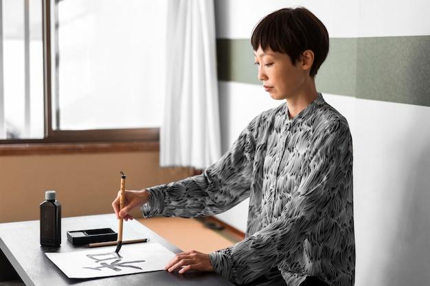 Mulher pintando com pincel de lado