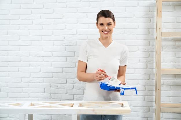 Mulher pintando com rack de madeira de cor branca