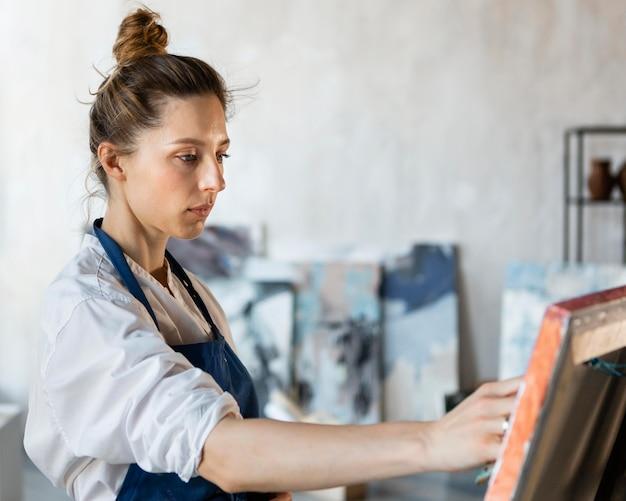 Mulher pintando dentro de casa