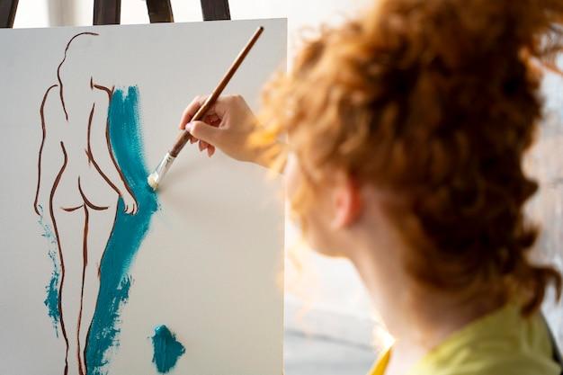 Mulher pintando em tela de perto