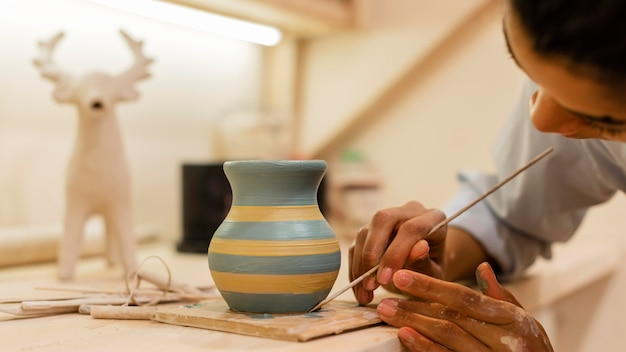 Mulher pintando panela de barro de perto