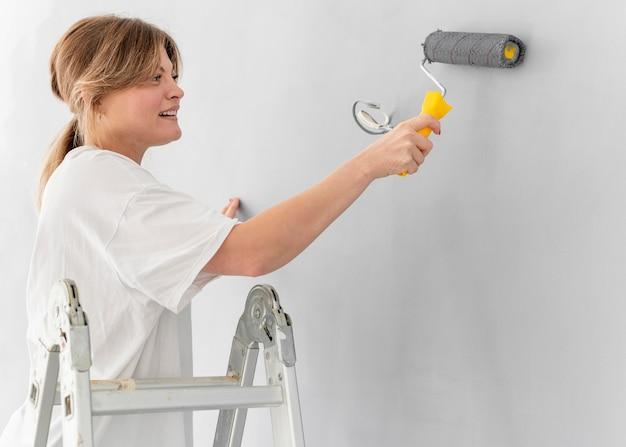 Mulher pintando parede com rolo