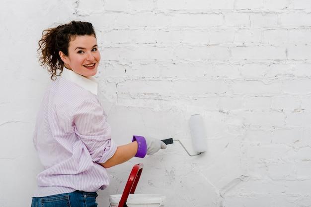Mulher pintando parede e olhando câmera