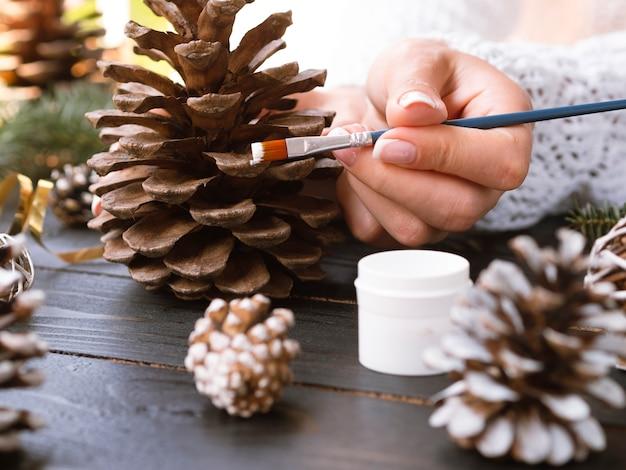 Mulher pintando pinha com tinta branca