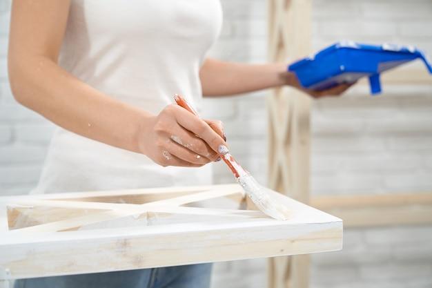 Mulher pintando rack de madeira com tinta branca