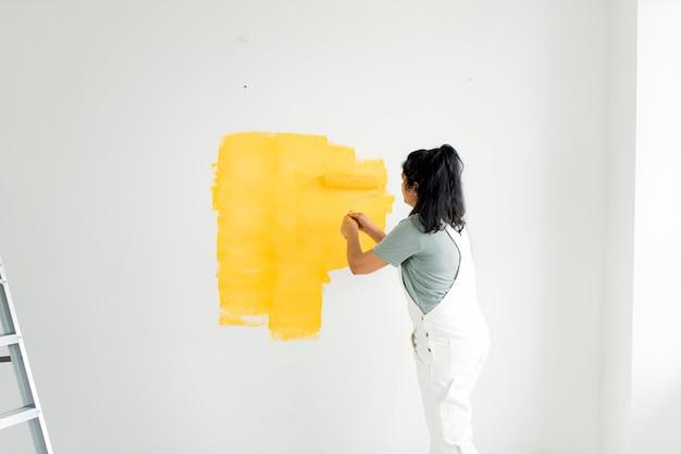 Mulher pintando suas paredes amarelas