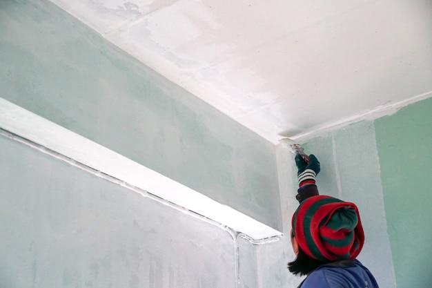 Mulher pintando teto com cor branca renovação