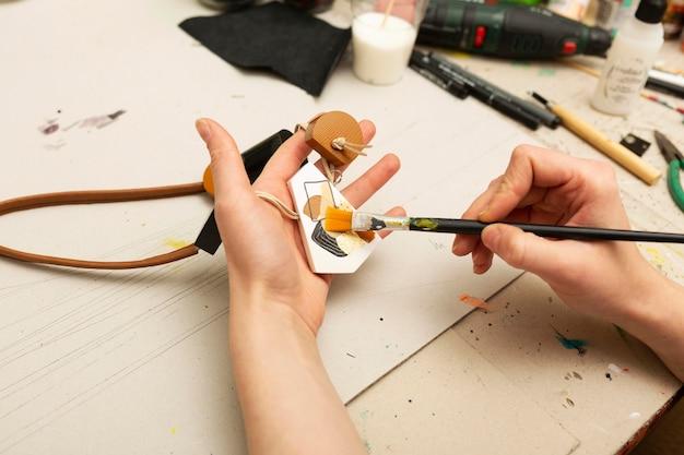 Mulher pintando um pequeno pedaço de madeira