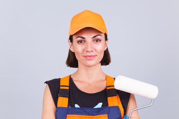 Mulher pintora com escova de rolo na parede cinza positiva sorrindo feliz