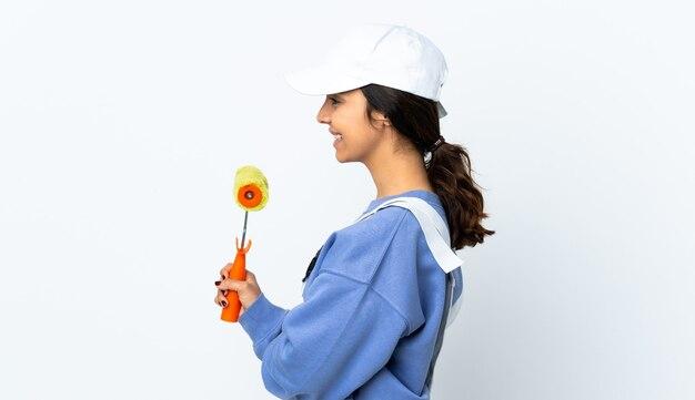 Mulher pintora sobre parede branca isolada em posição lateral