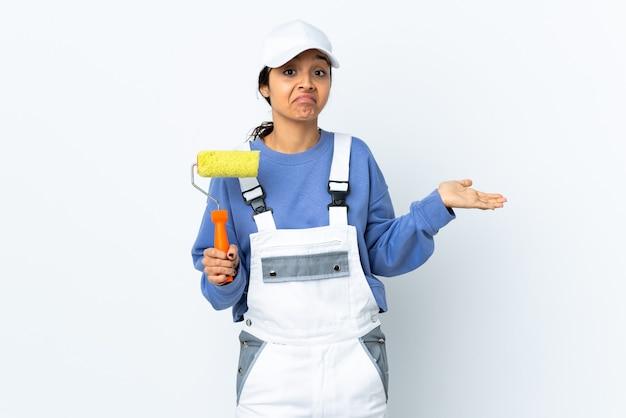 Mulher pintora sobre parede branca isolada, tendo dúvidas ao levantar as mãos