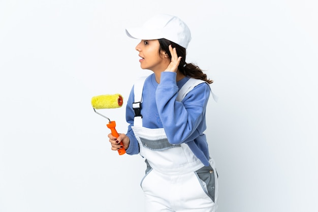 Mulher pintora sobre uma parede branca isolada, ouvindo algo colocando a mão no ouvido