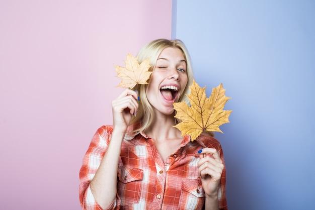 Mulher piscando em roupas casuais com tendências da moda de folhas amarelas para o outono mulher com folhas douradas