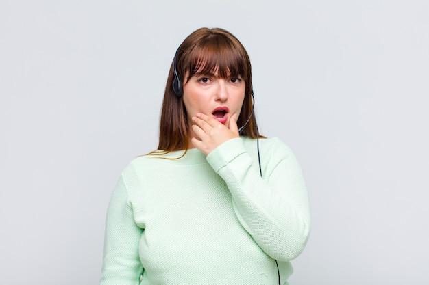 Mulher plus size com boca e olhos bem abertos e mão no queixo, sentindo-se desagradavelmente chocada, dizendo o quê ou uau