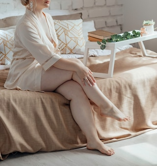 Mulher plus size com rosto irreconhecível sentada em uma cama dentro de casa usando lingerie e um robe de seda