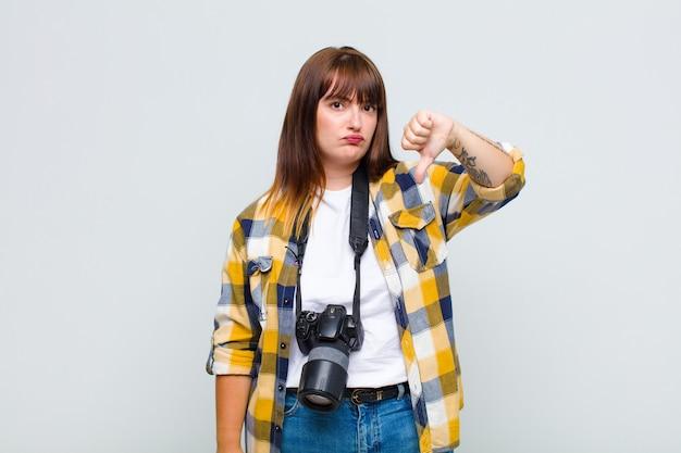 Mulher plus size sentindo-se zangada, irritada, irritada, decepcionada ou descontente, mostrando os polegares para baixo com um olhar sério