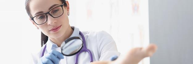 Mulher podólogo examinando o calcanhar do paciente usando lupa para tratamento de calosidades e
