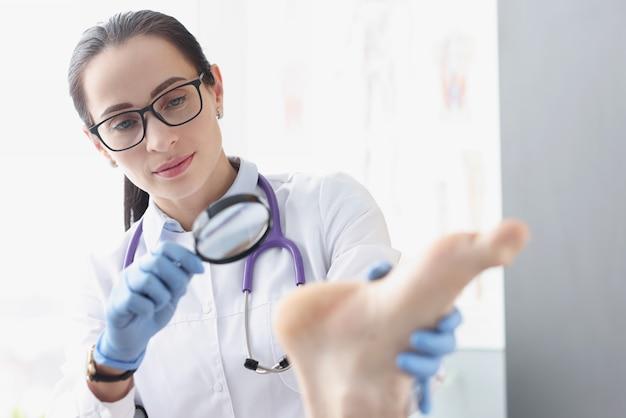 Mulher podólogo examinando o calcanhar do paciente usando uma lupa