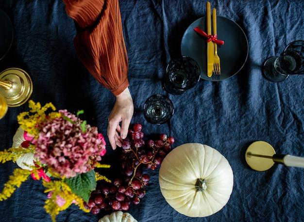 Mulher põe a mesa na véspera das férias de outono