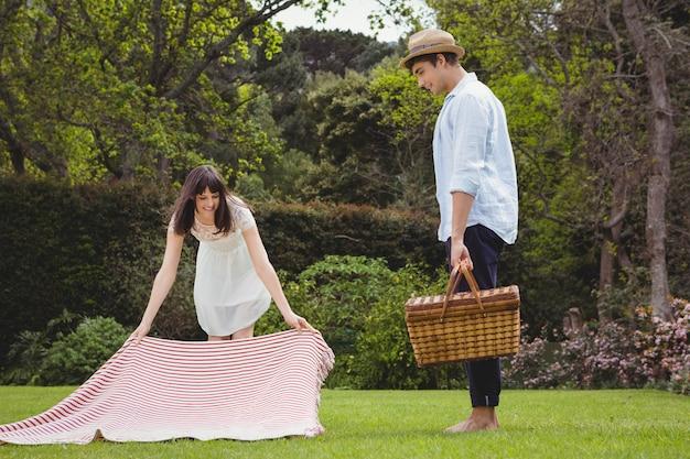 Mulher, pôr piquenique, cobertor, em, jardim, e, posição homem, com, cesta piquenique