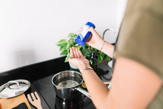 Mulher, pôr, sal, mão, enquanto, preparar, alimento, sobre, a, indução, fogão