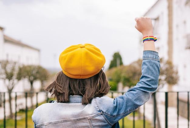 Mulher por trás com as mãos para cima e pulseira de arco-íris lgbt, foto vertical
