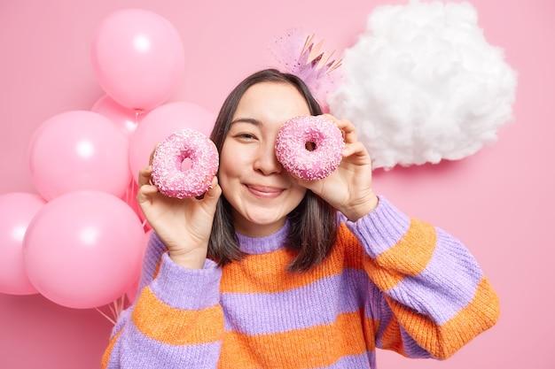 Mulher posa com deliciosos donuts com glacê no rosto tem humor feliz gosta de festejar usa macacão de manga comprida come sobremesa deliciosa.