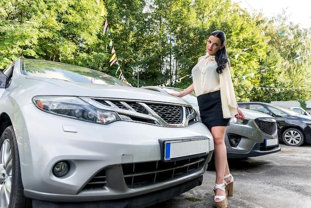 Mulher posando ao ar livre perto de um carro novo no estacionamento