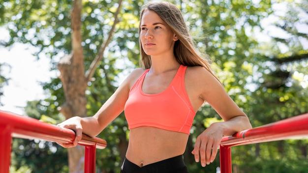 Mulher posando ao lado de duas barras de metal vermelhas