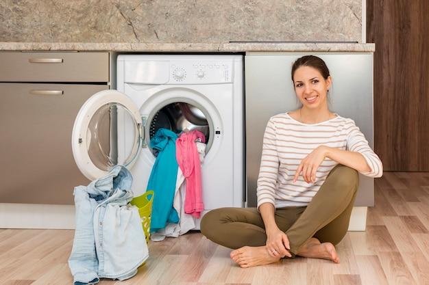 Mulher posando ao lado de máquina de lavar roupa