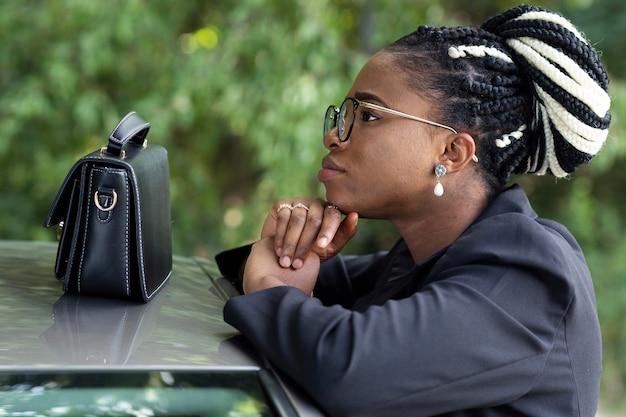 Mulher posando ao lado do carro com uma bolsa em cima