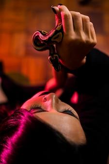 Mulher posando com cobra na parede escura