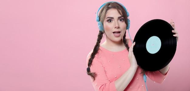Mulher posando com fones de ouvido e segurando o disco de vinil