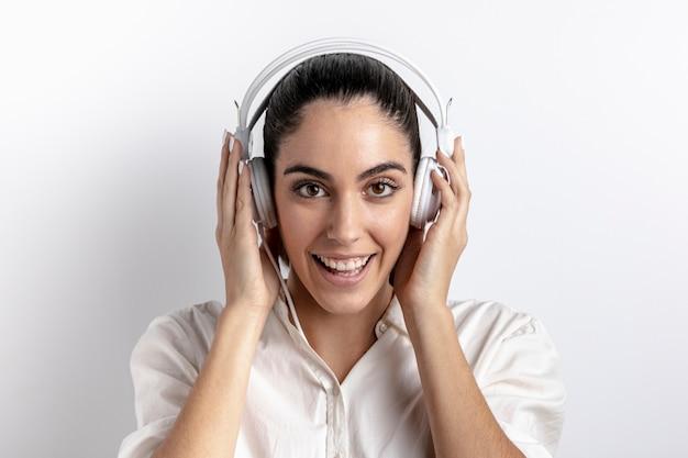 Mulher posando com fones de ouvido e sorrindo