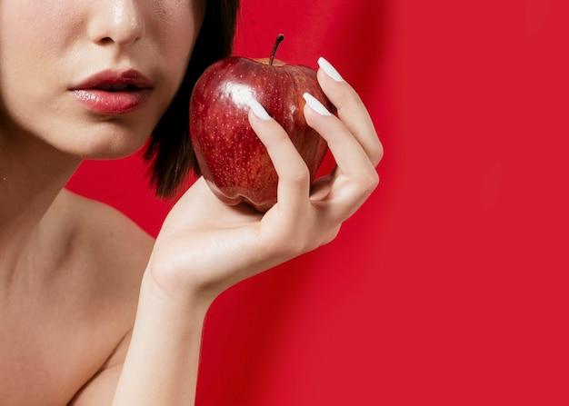 Mulher posando com maçã perto da boca