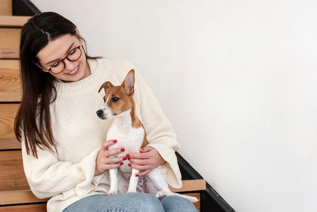 Mulher posando com seu cachorro na escada
