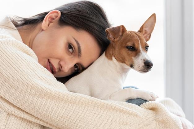 Mulher posando com seu cachorro nos braços