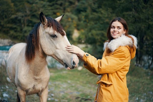 Mulher posando com um burro na natureza nas montanhas
