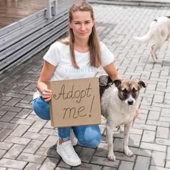 Mulher posando com um cachorro e segurando um cartaz de adote-me para animal de estimação